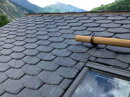 Сланцевая крыша с декоративной кладкой и мансардным окном